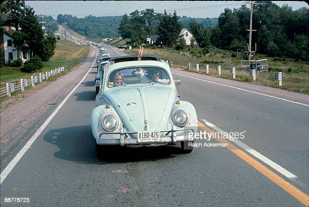 A man driving a Volkswagen Beatle on the way to the Woodstock Music Fetival flashes a peace sign through the sun roof of the car Bethel NY August...