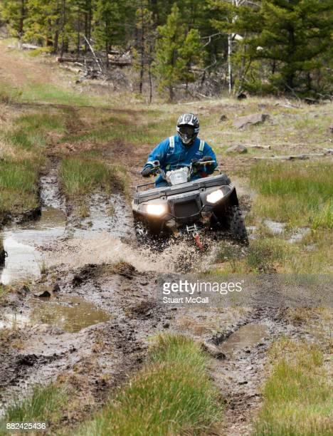 Man driving all terrain vehicle through mud.