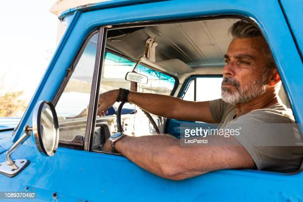 man driving an old pick-up truck in california roads - pick up truck stock pictures, royalty-free photos & images