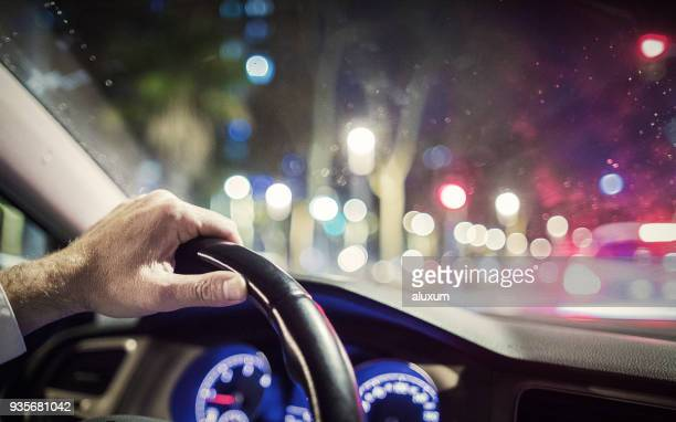 man driving at night in the city - steering wheel stock pictures, royalty-free photos & images