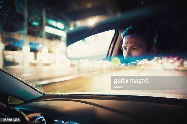 man driving at night in the city - rear view mirror stock pictures, royalty-free photos & images