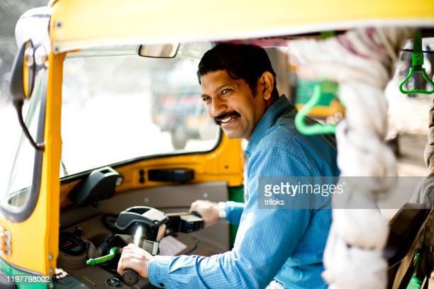 man driving auto rickshaw - rickshaw stock pictures, royalty-free photos & images