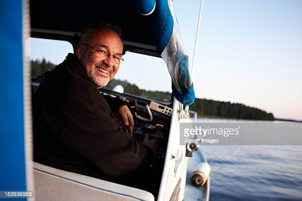 Man driving boat, smiling