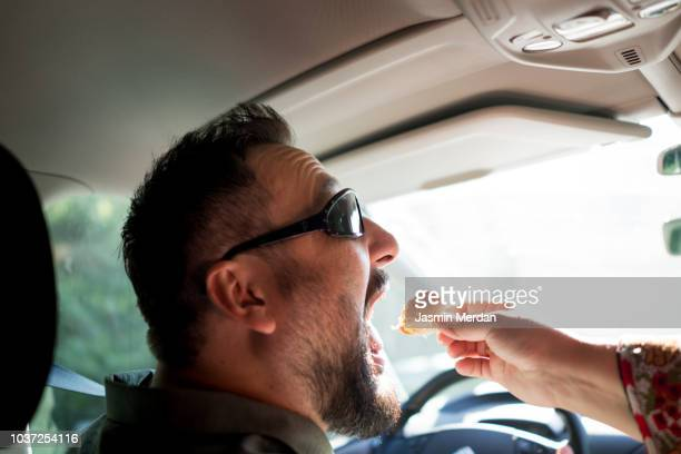 man driving car and eating food - wirkliches leben stock-fotos und bilder