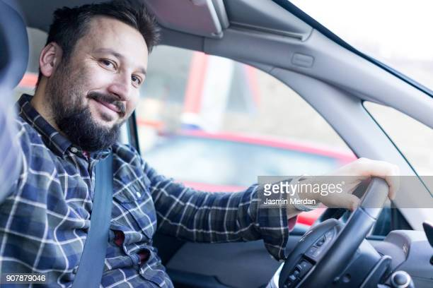 man driving car and taking selfie with mobile phone camera - saudi arabia stock photos and pictures