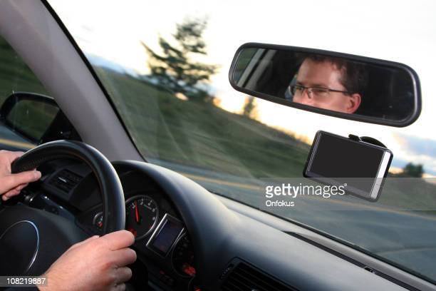 Man Driving Car Down Road with GPS Navigation Installed