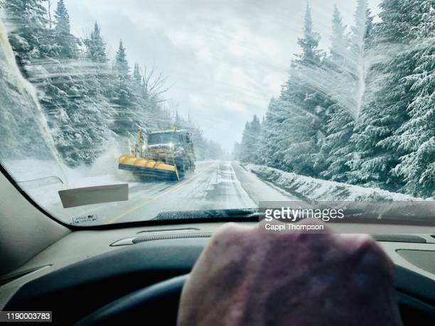 man driving car during winter in rangeley, maine with snowplow coming down road - 吹雪 ストックフォトと画像