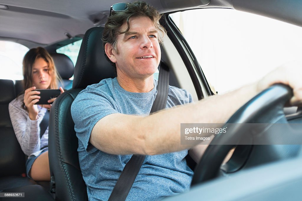 Man driving car, girl (10-11) texting in background : Stock Photo