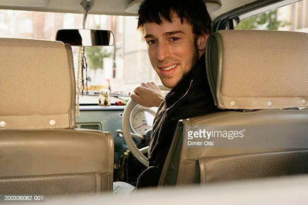 Man driving car, looking over shoulder, smiling, portrait