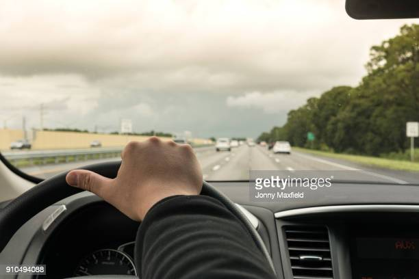 man driving car on highway, florida, usa, close up of hand and steering wheel - steering wheel stock pictures, royalty-free photos & images