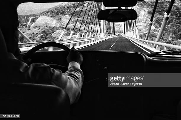 Man Driving Car On Suspension Bridge