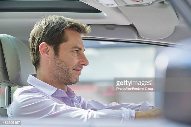 Man driving car, smiling