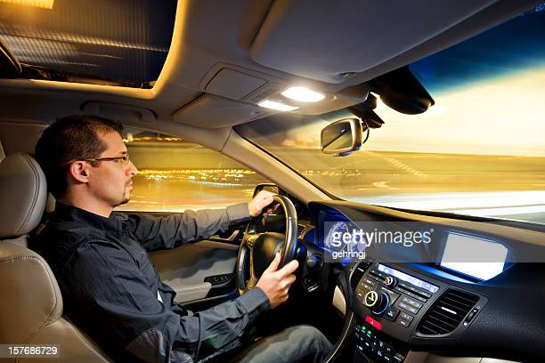 Man driving car with light interior at night