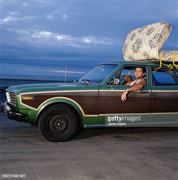 Man driving car with mattress strapped to roof, side view