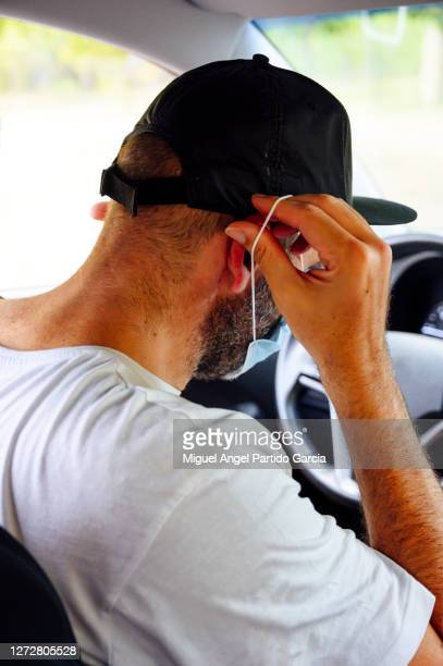 man driving car with protective mask - stock photo. - travelstock44 stock pictures, royalty-free photos & images