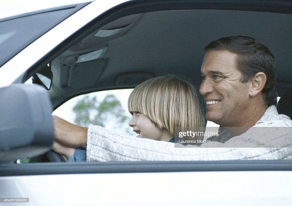 Man driving car with son on lap, side view : Stockfoto
