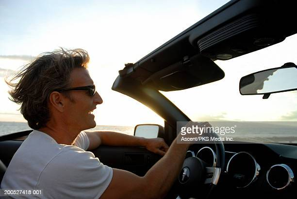 man driving convertible at sunset with wind in his hair, profile - convertible stock pictures, royalty-free photos & images