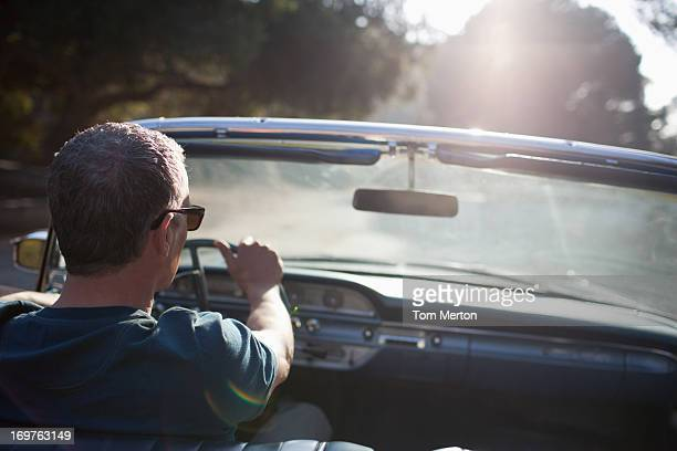 Man driving convertible car