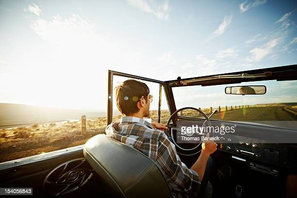 Man driving convertible on desert road at sunset