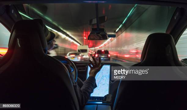 Man driving electric vehicle through Holland Tunnel, using autopilot technology