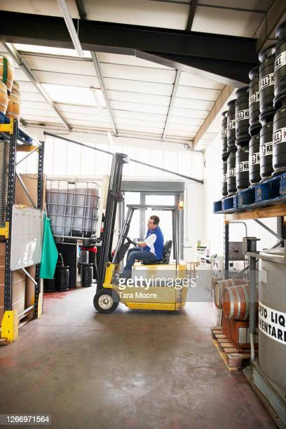 man driving forklift in warehouse - pallet industrial equipment stock pictures, royalty-free photos & images