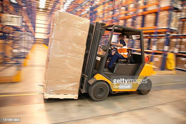 Man driving forklift in warehouse
