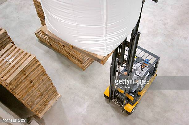 Man driving forklift truck in packaging plant, elevated view