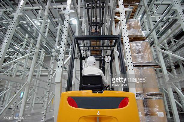 man driving forklift truck in packaging plant, rear view - man wrapped in plastic stock pictures, royalty-free photos & images