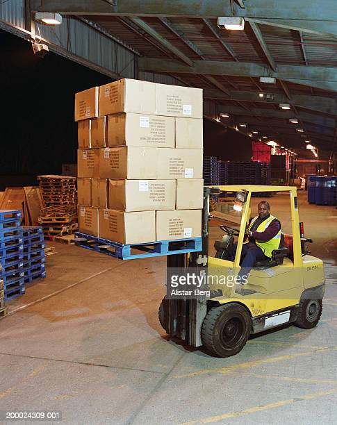 Man driving forklift truck in warehouse