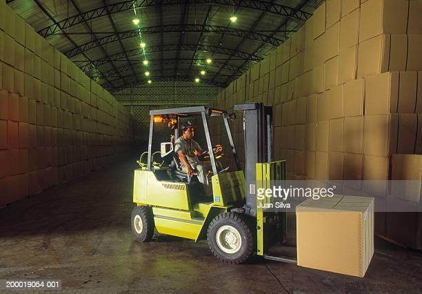 man driving forklift with boxes in warehouse - gabelstapler stock-fotos und bilder