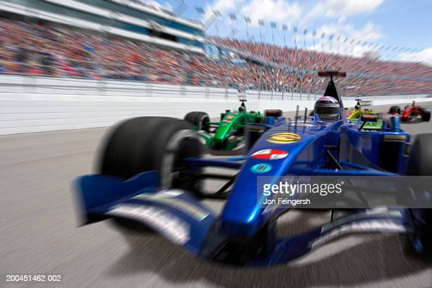 Man driving Formula 1 race car (Digital Composite, blurred motion)