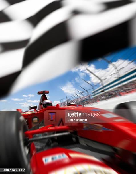 Man driving Formula 1 race car under flag (Digital Composite)