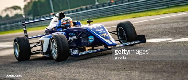 男運転フォーミュラレーシングカー - レーシングドライバー ストックフォトと画像