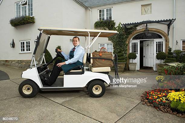 Man driving golf cart with luggage.