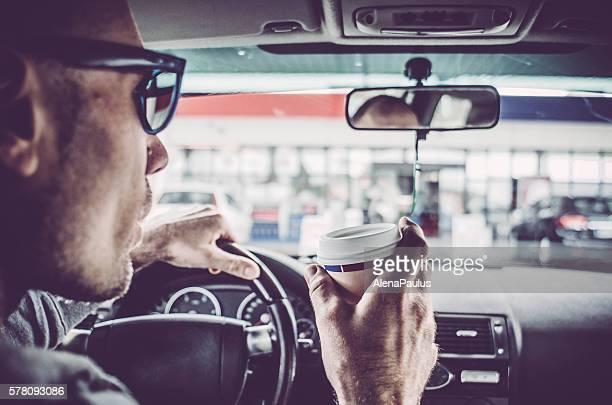 男 駆動車とバーでは、テイクアウトのコーヒーを
