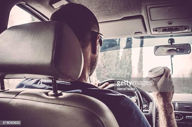 Mann sein Auto fahren und Trinken Kaffee zum Mitnehmen