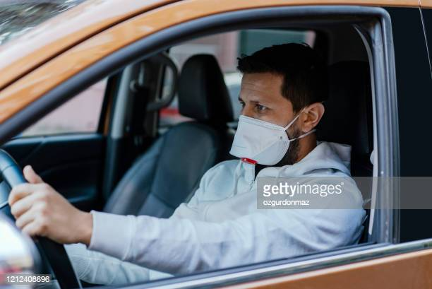 man driving his car with a protection mask in the city - driving mask stock pictures, royalty-free photos & images