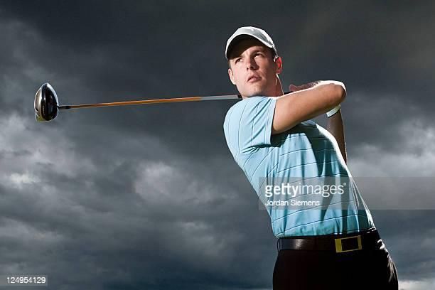 A man driving his golf ball.