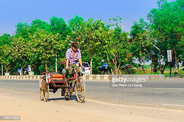 Man driving his trishaw without client on the street of Yangon, Myanmar on Mar 10, 2013