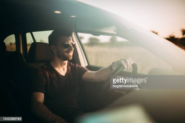 man driving in sunset - driver stock pictures, royalty-free photos & images