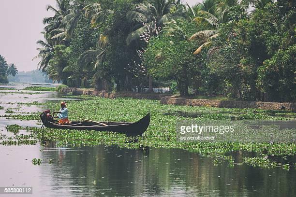 Man driving Kettuvallam on the Kerala Backwaters in India