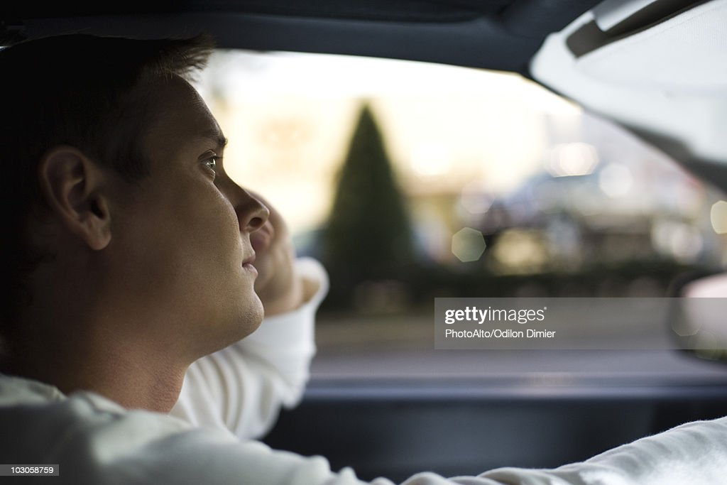 Man driving, lost in thought : Stock Photo