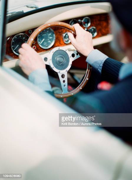 man driving luxury antique car - prestige car stock pictures, royalty-free photos & images