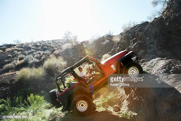 Man driving off-road vehicle over rocks