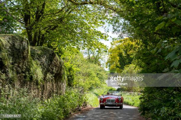 Man driving open top convertible MG sports car in The Cotswolds, England. .