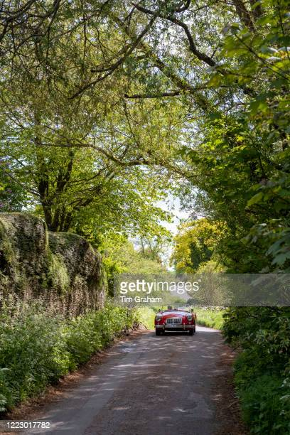 Man driving open top convertible MG sports car in The Cotswolds England