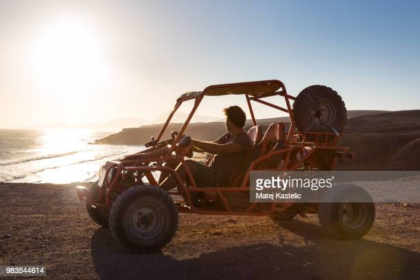 Man driving quadbike in sunset.