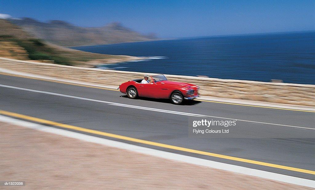 Man Driving Red Sports Car Along Coastal Road : Stock Photo