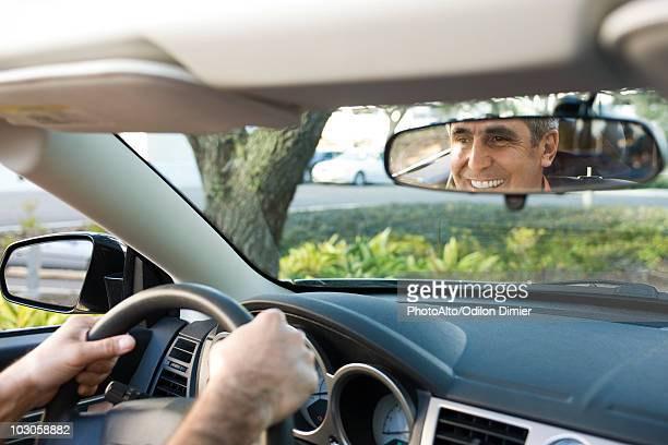 Man driving, reflection in rearview mirror