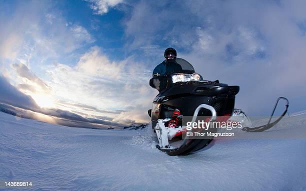 man driving snowmobile in snowy field - snowmobiling - fotografias e filmes do acervo